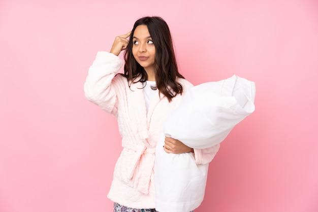 Jeune femme en pyjama isolé sur mur rose ayant des doutes et de la pensée
