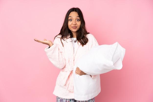 Jeune femme en pyjama isolé sur mur rose ayant des doutes tout en levant les mains