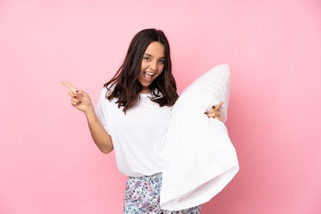 Jeune femme en pyjama isolé sur le mur rose, pointant le doigt vers les côtés et heureux