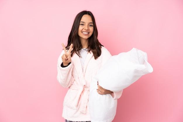 Jeune femme en pyjama isolé sur mur rose souriant et montrant le signe de la victoire