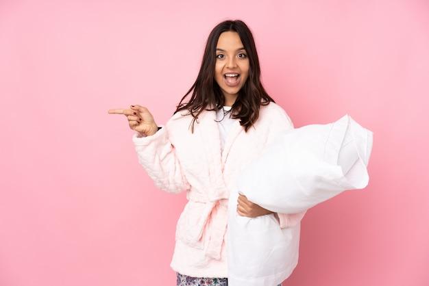 Jeune femme en pyjama isolé sur mur rose surpris et pointant le doigt sur le côté