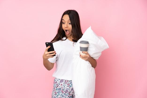 Jeune femme en pyjama isolé sur mur rose tenant du café à emporter et un mobile
