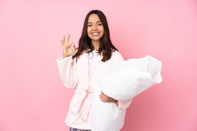 Jeune femme en pyjama isolé sur rose