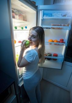 Jeune femme en pyjama mangeant de la pizza au réfrigérateur ouvert la nuit