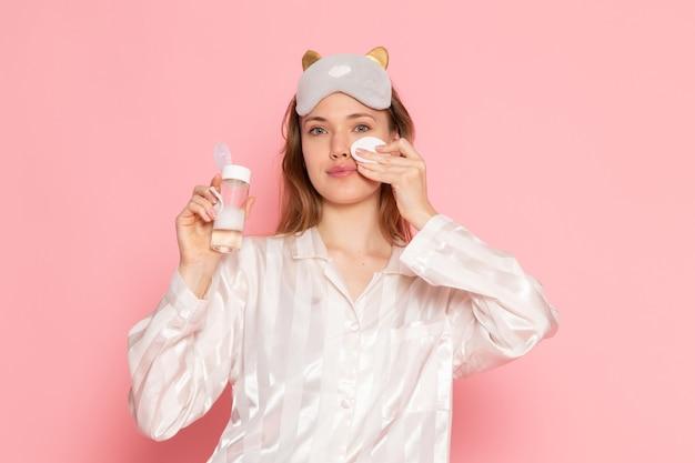 Jeune femme en pyjama et masque de sommeil à l'aide de spray de maquillage sur rose