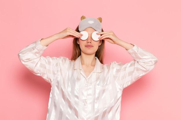 Jeune femme en pyjama et masque de sommeil nettoyant son visage sur rose