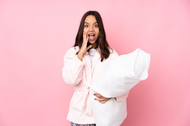 Jeune femme en pyjama sur mur rose avec une expression faciale surprise et choquée