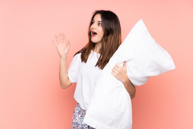 Jeune femme en pyjama sur mur rose avec une expression faciale surprise