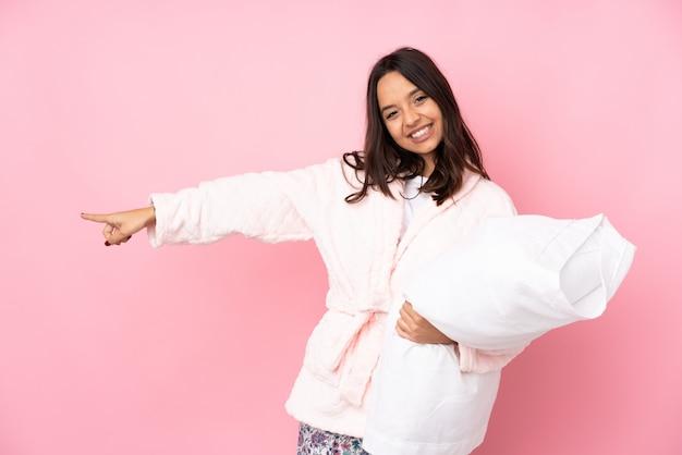 Jeune femme en pyjama sur le mur rose, pointant le doigt sur le côté
