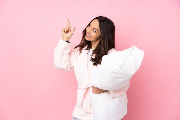 Jeune femme en pyjama sur mur rose pointant avec l'index une excellente idée