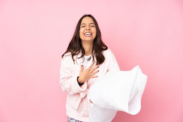 Jeune femme en pyjama sur mur rose souriant beaucoup