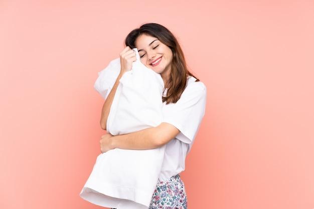 Jeune femme en pyjama sur mur rose