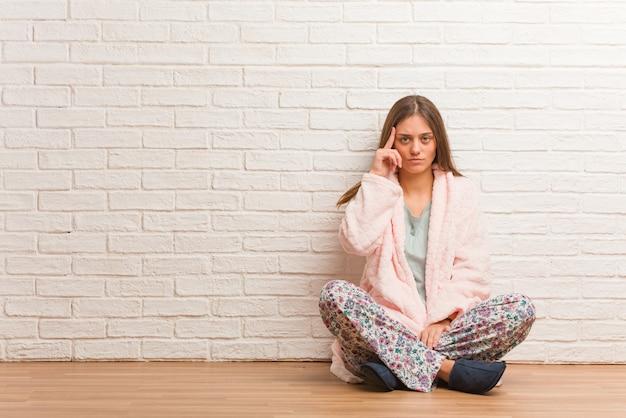 Jeune femme en pyjama réfléchissant à une idée