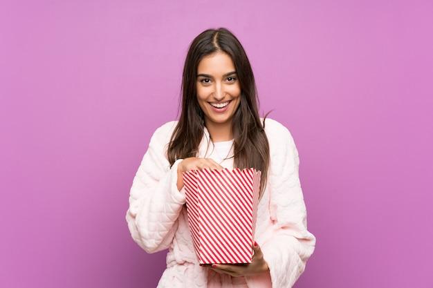 Jeune femme en pyjama et robe de chambre sur un mur violet isolé, tenant des pop-corn