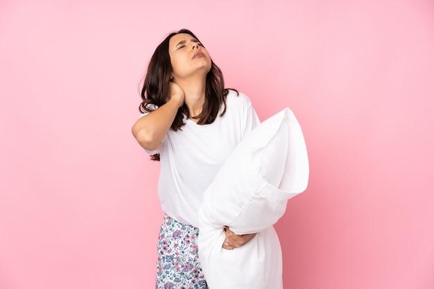 Jeune femme en pyjama sur rose avec maux de cou