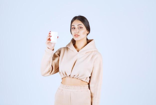Jeune femme en pyjama rose tenant une tasse de boisson
