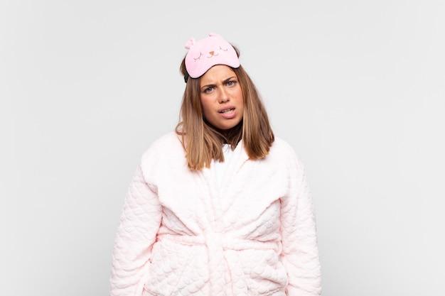Jeune femme en pyjama, se sentant perplexe et confus