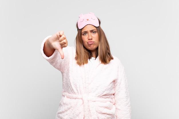 Jeune femme en pyjama, se sentir croisé, en colère, ennuyé, déçu ou mécontent, montrant les pouces vers le bas avec un regard sérieux