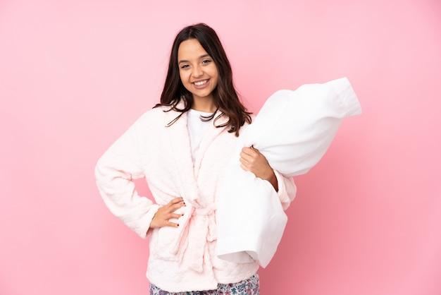 Jeune, femme, pyjamas, isolé, rose, poser, bras, hanche, sourire