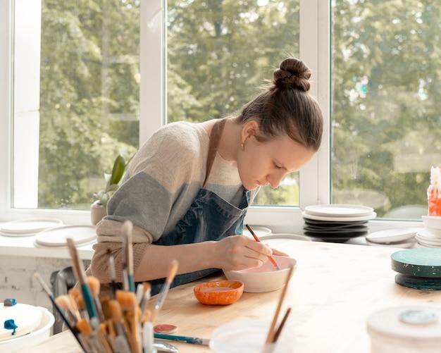 Jeune femme qualifiée en tablier assis à table et s'appuyant sur un bol en céramique dans l'atelier de poterie