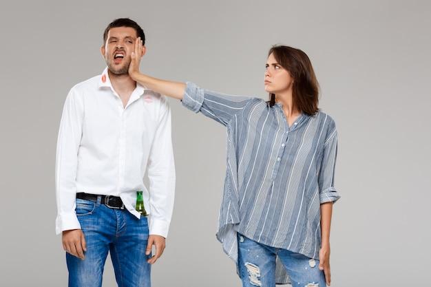 Jeune femme, querelle, colère, à, ivre, mari, sur, mur gris