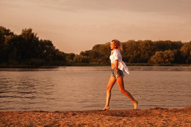 Une jeune femme qui court au bord de la rivière au coucher du soleil photo de profil d'une belle blonde heureuse en cl...