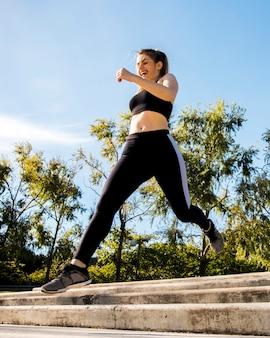 Jeune femme qui court à l'extérieur avec des vêtements de sport