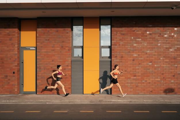 Jeune femme qui court sur le trottoir le matin. concept soucieux de la santé. mode de vie sain et actif.