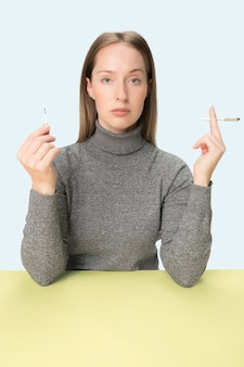 La jeune femme qui fume la cigarette alors qu'elle était assise à table au studio. couleurs à la mode. le portrait de fille caucasienne dans un style minimalisme avec espace copie