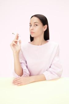 La jeune femme qui fume une cigarette assise à table au studio.