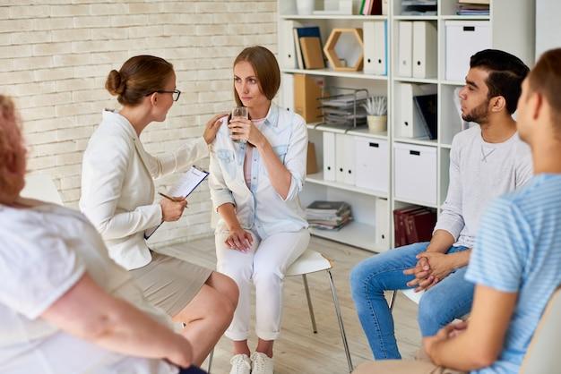 Jeune femme qui pleure en séance de thérapie de groupe