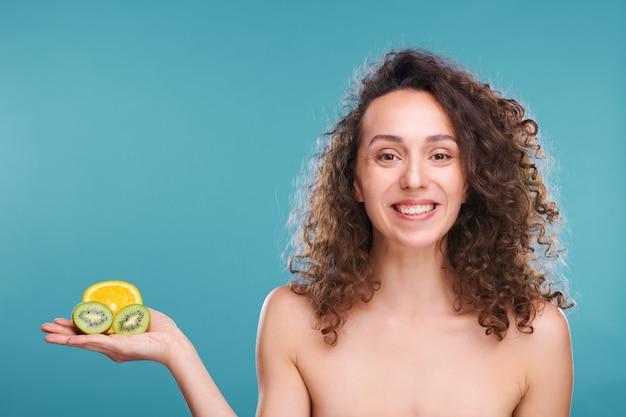 Jeune femme qui rit avec un sourire à pleines dents et de longs cheveux ondulés foncés tenant la moitié d'orange juteuse et de kiwi frais sur ses paumes de manière isolée