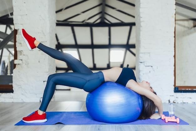 Jeune femme qui s'étend sur une boule bleue à la salle de sport