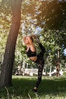 Jeune femme qui s'étend dans le parc