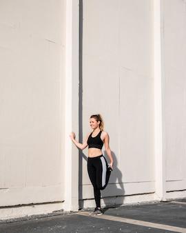 Jeune femme qui s'étend dans la rue