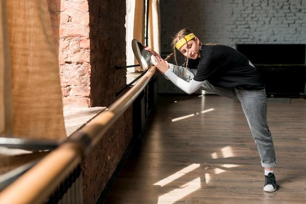 Jeune femme qui s'étend de la jambe sur la barre dans le studio de danse