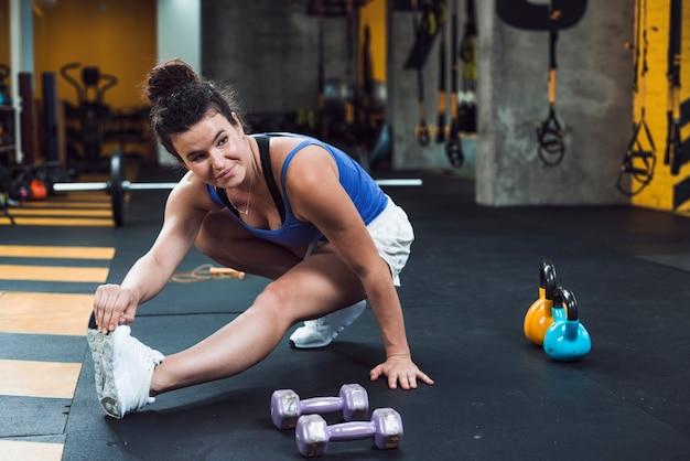 Jeune femme qui s'étend de la jambe dans la salle de gym