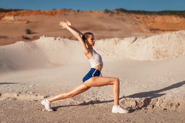 Jeune femme qui s'étend de jambes et se réchauffe à la nature. jolie fille qui s'étend avant la forme physique. belle fille sportive faisant du fitness en plein air. faites la posture de guerrier de yoga.