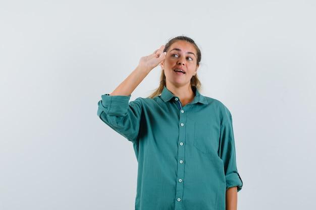 Jeune femme qui s'étend de la main comme salutation quelqu'un en chemisier vert et à la recherche de plaisir