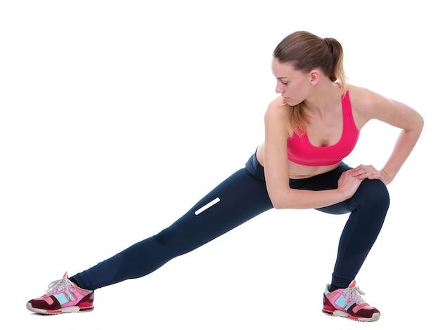 Jeune femme qui s'étend les muscles des jambes