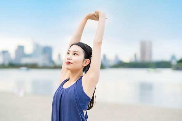 Jeune femme qui s'étend et prend une profonde respiration sur la plage de la ville