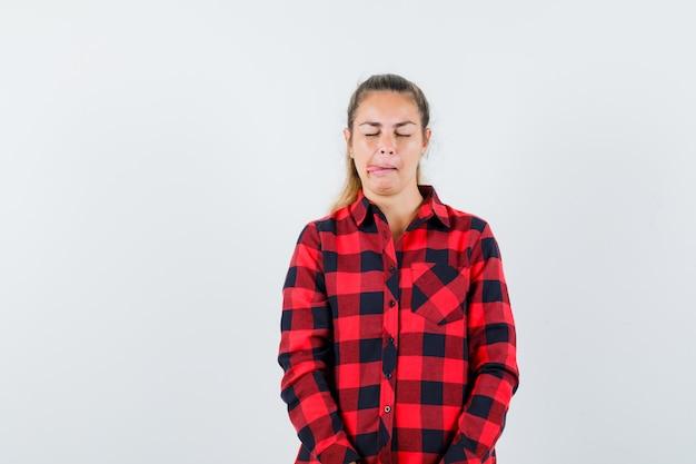 Jeune femme qui sort la langue en chemise à carreaux et à la rêveuse, vue de face.