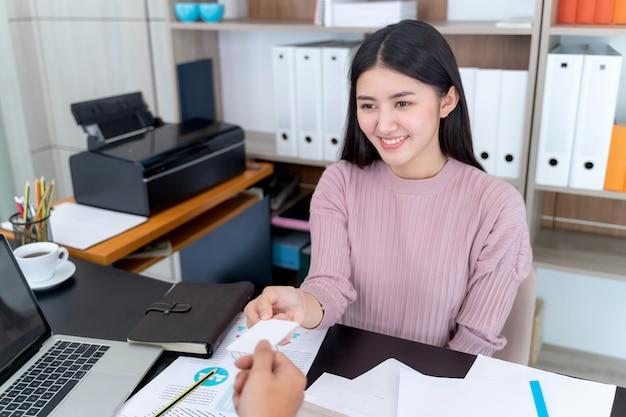 Jeune femme qui travaille reçoit une carte de visite de l'homme d'affaires
