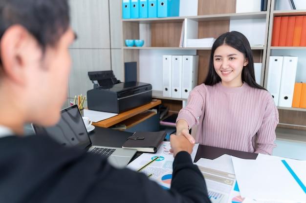 Jeune femme qui travaille vérifie les mains avec un homme d'affaires