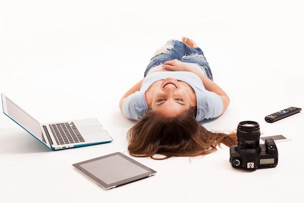 Jeune femme de race blanche avec des appareils électroniques