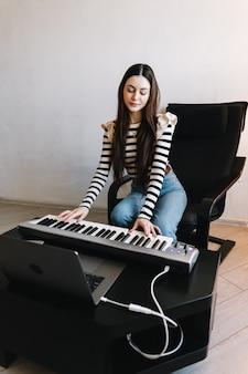 Jeune femme de race blanche apprend à jouer les touches du piano à l'aide d'un ordinateur portable à la maison à distance.