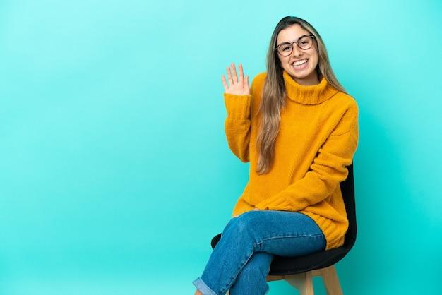 Jeune femme de race blanche assise sur une chaise isolée sur fond bleu saluant avec la main avec une expression heureuse