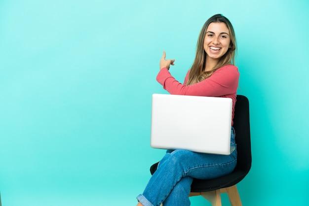 Jeune femme de race blanche assise sur une chaise avec son pc isolé sur fond bleu pointant vers l'arrière