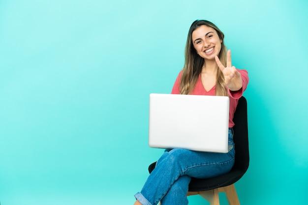 Jeune femme de race blanche assise sur une chaise avec son pc isolé sur fond bleu souriant et montrant le signe de la victoire