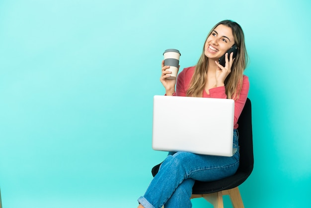 Jeune femme de race blanche assise sur une chaise avec son pc isolé sur un mur bleu tenant du café à emporter et un mobile